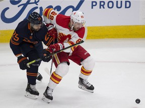 Edmonton Oilers Darnell Nurse (25) battles for the puck with Calgary Flames Nikita Nesterov (89) during first period NHL action on Saturday, Feb. 20, 2021 in Edmonton.