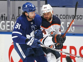 Zack Kassian (44) of the Edmonton Oilers battles against John Tavares (91) of the Toronto Maple Leafs during an NHL game at Scotiabank Arena on March 27, 2021, in Toronto.
