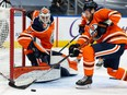 Edmonton Oilers goaltender Mike Smith (41) defends his crease with Adam Larsson (6) without a stick as he battles the Ottawa Senators during second period NHL action at Rogers Place in Edmonton, on Friday, March 12, 2021.