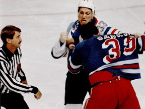 Edmonton Oilers tough guy Marty McSorley punches it out with New York Rangers Terry Carkner as NHL linesman Swede Knox stands by in 1987 at Northlands Coliseum in Edmonton.