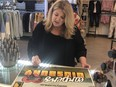 """Karen Duggan, owner of Ulla La Boutique, with a sign business owners are putting in their windows in Didsbury to support Wynonna Earp and push for a fifth season. Ella La Boutique plays """"Shorty's"""" in the series, which is partially filmed in Didsbury. Courtesy, Keep Alberta Rolling"""