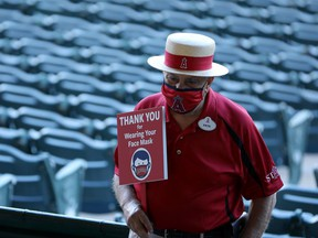"An usher holds a sign that reads, ""Thank You for Wearing Your Face Mask"" before the game between the Los Angeles Angels and the Chicago White Sox at Angel Stadium of Anaheim earlier this month."