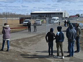 Supporters are seen outside the property of GraceLife Church in Parkland County on Thursday, April 8, 2021, after officials fenced off the church on Wednesday.