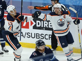 Edmonton Oilers centre Connor McDavid (right) celebrates his goal against the Winnipeg Jets with Jesse Puljujarvi in Winnipeg on April 26, 2021.