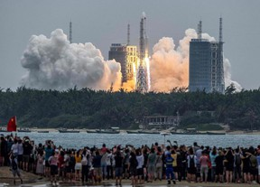 TOPSHOT - People watch a Long March 5B rocket, carrying China's Tianhe space station core module, as it lifts off from the Wenchang Space Launch Center in southern China's Hainan province on April 29, 2021. (Photo by STR / AFP) / China OUT