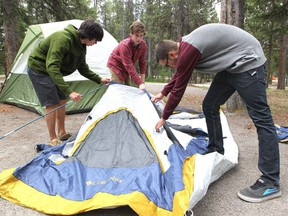 Friends Brandon Line, Connor Lengkeek and Tristan Hughes set up their tent at the Tunnel Mountain campground in Banff National Park on May 17, 2013.