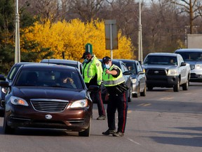 Motorists are stopped at a police checkpoint after new coronavirus disease (COVID-19) restrictions came into effect, limiting travel into the province of Ontario, in Ottawa, Ontario, Canada April 19, 2021.
