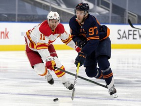 The Edmonton Oilers' Connor McDavid (97) battles the Calgary Flames' Mikael Backlund (11) during third period NHL action at Rogers Place, in Edmonton Thursday April 29, 2021. The Flames won 3-1.