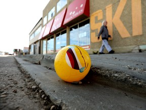A pedestrian makes their way past an inflatable ball, with a crying laughing emoji graphic, laying in the gutter along 79 Avenue near 105 Street, in Edmonton Wednesday May 12, 2021. Photo by David Bloom