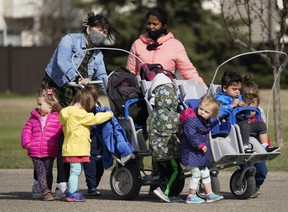 Two daycare workers take a group of children out for a walk in west Edmonton on Thursday May 6, 2021.