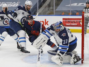 Winnipeg Jets goaltender Connor Hellebuyck (37) makes a save with Edmonton Oilers forward Kailer Yamamoto (56) looking for a rebound during the first period in game one of the first round of the 2021 Stanley Cup Playoffs at Rogers Place on May 19, 2021.