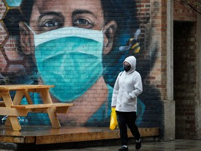 A woman walks past a wall mural in downtown Edmonton during the COVID-19 pandemic on Tuesday, May 18, 2021.