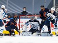 Winnipeg Jets goalie Connor Hellebuyck stops a shot by Edmonton Oilers forward James Neal, left, as Oilers forward Zack Kassian and Jets defenceman Logan Stanley, at right, look on during NHL playoff action on May 19, 2021, at Rogers Place.