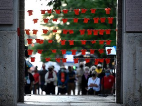 Orange fabric cut in the shape of shirts are pinned to string at the Human Right's Monument in Ottawa, during a vigil held by Ottawa faith communities, to honour the 215 children whose remains were found at the grounds of the former Kamloops Indian Residential School at Tk'emlups te Secwépemc First Nation in Kamloops, B.C., on Saturday, June 5, 2021.