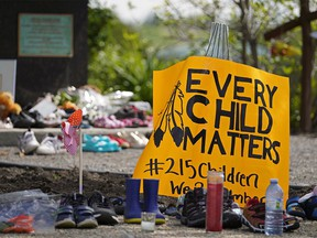 Hundreds of children's shoes remain in place at a memorial outside the Alberta Legislature building in Edmonton on Monday May 31, 2021. A vigil was held Sunday May 30, 2021 in memory of the 215 indigenous children whose remains were discovered on the grounds of a former Roman Catholic church residential school in Kamloops, B.C.