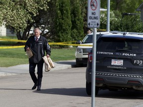An ASIRT investigator is seen carrying bags of evidence to his vehicle on Sunday, June 6, 2021 after man was shot and killed in a confrontation with police near 134 Avenue and 107 Street in Edmonton's Rosslyn neighbourhood on Saturday night.