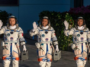 Chinese astronauts from China's Manned Space Agency, left to right, Tang Hongbo, Nie Haisheng, and Liu Boming wave at a departure ceremony before launch of the Senzhou-12 at the Jiuquan Satellite Launch Center on June 17, 2021 in Jiuquan, Gansu province, China.