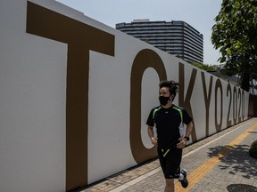 TOKYO, JAPAN - JULY 12: A man wearing a face mask runs past a Tokyo 2020 banner on July 12, 2021 in Tokyo, Japan. Japan entered its fourth state of emergency today as the government tries to contain a resurgence in coronavirus infections with less than two weeks to go before the start of the postponed Olympic Games.