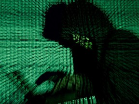 A man holds a laptop computer as cyber code is projected on him in this illustration picture taken on May 13, 2017.