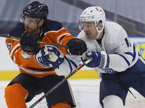 The Edmonton Oilers defence man Adam Larsson (6) battles the Toronto Maple Leafs' Zach Hyman (11) during second period NHL action at Rogers Place, in Edmonton Saturday Feb. 27, 2021.