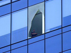 A man looks out from a broken window on the Stantec Tower in downtown Edmonton on Wednesday July 28, 2021. Police closed off the road at the base of the tower for hours while crews dealt with the issue. Larry Wong, Postmedia