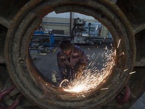 A worker works on a part from a rock crusher at Universe Machine, an Edmonton manufacturing company. File photo.