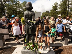 Children lay tulips at the feet of a statue of Anne Frank that was unveiled at Light Horse Park in Edmonton, on Sunday, Aug. 8, 2021. The statue was installed by the Dutch Canadian Club as part of their 75th Liberation Project. Photo by Ian Kucerak