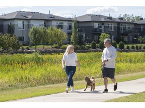 Jennifer and Dino Cairo walk their dog, Cooper, in the neighbourhood of their soon-to-be-built home in Drive at Windermere.