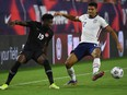 Canada midfielder Alphonso Davies (19) plays the ball past United States defender Miles Robinson (12) in the first half during a CONCACAF FIFA World Cup Qualifier soccer match at Nissan Stadium on Sept. 5, 2021.