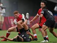 Canada's Connor Braid (L) attempts to carry the ball past New Zealand's Andrew Knewstubb (bottom) in the men's quarter-final rugby sevens match between New Zealand and Canada during the Tokyo 2020 Olympic Games at the Tokyo Stadium in Tokyo on July 27, 2021.