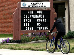 A cyclist, wearing a protective COVID-19 face mask, makes their way past a sign at Calvary Lutheran Church, 10815 76 Ave., in Edmonton on Aug. 22, 2021.