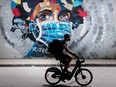 In Montreal, a man wears a face mask as he cycles by a mural defaced by graffiti objecting to mask usage to protect against the spread of COVID-19, on Aug 30, 2020,