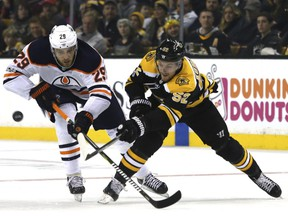 Edmonton Oilers center Leon Draisaitl (29) and Boston Bruins center Sean Kuraly (52) vie for the puck during the second period of an NHL hockey game in Boston, Sunday, Nov. 26, 2017.