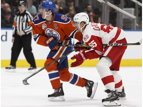 Edmonton's Connor McDavid (97) is held by Detroit's Danny DeKeyser (65) during the second period of a NHL game between the Edmonton Oilers and the Detroit Red Wings at Rogers Place in Edmonton on Saturday, March 4, 2017.