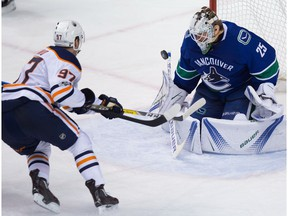 Edmonton Oilers' Connor McDavid, left, puts a shot wide of the net behind Vancouver Canucks goalie Jacob Markstrom, of Sweden, during the third period of an NHL hockey game in Vancouver, B.C., on Saturday, October 7, 2017.