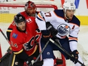 Calgary Flames defenceman Travis Hamonic battles Milan Lucic of the Edmonton Oilers during NHL action at the Scotiabank Saddledome in Calgary on  September 18, 2017.
