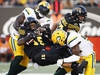 Hamilton Tiger-Cats' Alex Green gets tackled by Edmonton Eskimos Almondo Sewell, left, and Alex Bazzie, right, during the first half of CFL football action in Hamilton, Ontario on Thursday August 23, 2018. THE CANADIAN PRESS/Mark Blinch ORG XMIT: MDB117