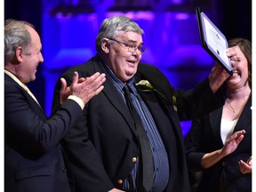 Sports Columnist Terry Jones holds up his award after being inducted into the Sports Hall of Fame during the Salute to Excellence Hall of Fame Induction Ceremony at the Winspear Centre in Edmonton June 11, 2018.