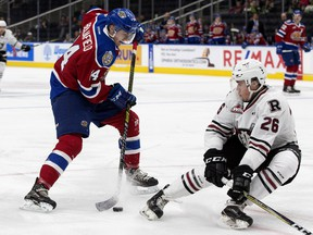 The Edmonton Oil Kings' Quinn Benjafield (14) battles the Red Deer Rebels' Chase Leslie (26) during first period WHL action at Rogers Place, in Edmonton Friday Oct. 19, 2018. Photo by David Bloom