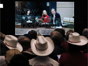 An overflow crowd in the lobby of City Hall watches as Calgary 2026 BidCo's Mary Moran and Scott Scott Hutcheson answer council questions before a vote on a motion to end the 2026 Olympic bid process on Wednesday October 31, 2018.  Gavin Young/Postmedia