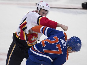 Edmonton Oilers Milan Lucic (27) Calgary Flames Anthony Peluso (16) exchange blows during first period NHL action on Sunday, Dec. 9, 2018, in Edmonton.