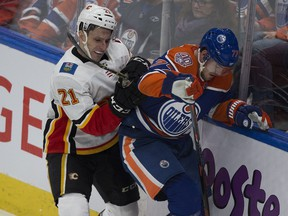 Edmonton Oilers Oscar Klefbom (77) and Calgary Flames Garnet Hathaway (21) battle for the puck during second period NHL action on Sunday, Dec. 9, 2018, in Edmonton.