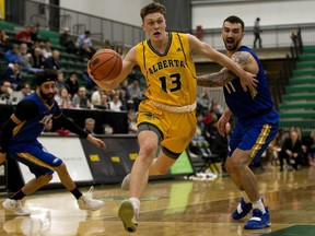 The University of Alberta Golden Bears' Adam Paige (13) breaks past the UBC Thunderbirds' Manroop Clair (3) and Patrick Simon (11) during Game 3 of their Canada West playoff series, in Edmonton Sunday Feb. 24, 2019.