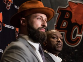 B.C. Lions general manager Ed Hervey, back, and quarterback Mike Reilly listen during a news conference after Reilly signed a four-year contract with the team, in Surrey, B.C., on Feb. 12, 2019.