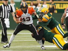 Edmonton Eskimos' Almondo Sewell (90) and Martese Jackson (30) tackle BC Lions' quarterback Mike Reilly (13) during a CFL football game at Commonwealth Stadium in Edmonton, on Friday, June 21, 2019.
