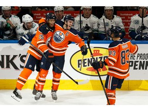 Edmonton Oilers' Connor McDavid (97) celebrates his goal with Darnell Nurse (25) and Matt Benning (83) on Vancouver Canucks' goaltender Jacob Markstrom (25) during third period NHL action at Rogers Place in Edmonton, on Wednesday, Oct. 2, 2019.