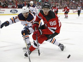 CP-Web.  Edmonton Oilers defenseman Ethan Bear (74) defends New Jersey Devils center Jack Hughes (86) during the second period of an NHL hockey game Thursday, Oct. 10, 2019, in Newark, N.J.