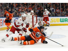 Edmonton Oilers' Ryan Nugent-Hopkins (93) is tripped by Carolina Hurricanes' Brett Pesce (22) during the third period of a NHL hockey game at Rogers Place in Edmonton, on Tuesday, Dec. 10, 2019.