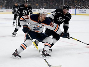 Connor McDavid #97 of the Edmonton Oilers fends off Derek Forbort #24 of the Los Angeles Kinfgs rom the puck during the first period at Staples Center on February 23, 2020 in Los Angeles, California.