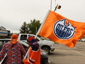 Edmonton Oilers superfan Blair Gladue (left) and his brother Clayton Cardinal celebrate with hockey fans after cheering from the bridge at St. Albert Trail and Anthony Henday Drive after hearing about the resumption of the NHL playoffs in Edmonton on May 26, 2020.